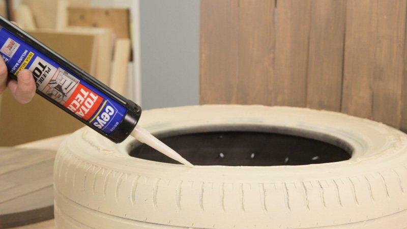 Aplicar cola blanca al neumático para pegar la tabla de madera del asiento.