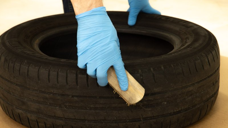 Limpiar el neumático con un cepillo antes de pintarlo con la pintura de spray.