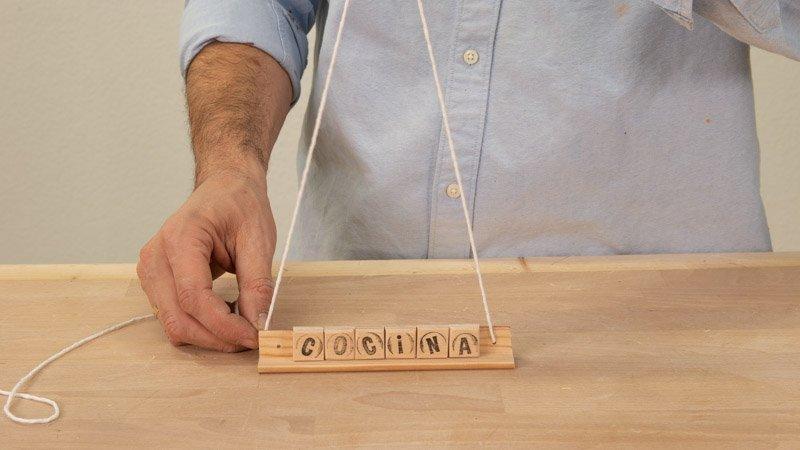 Colocar las cuerdas en el soporte para colgar el cartel de madera para la cocina.