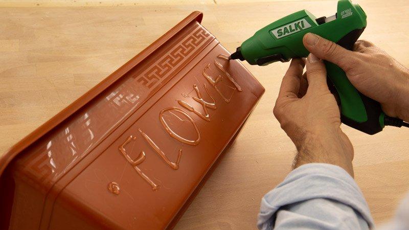 Pistola de silicona Salki decorando una maceta con cola caliente