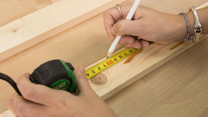 Lápiz marcando las diferentes medidas de los listones de madera