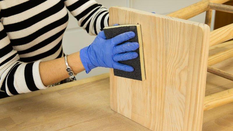 Lijado del taburete de madera para restaurarlo