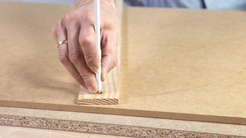 Marcar el diámetro del neumático en la madera que será la base del asiento de madera con respaldo.