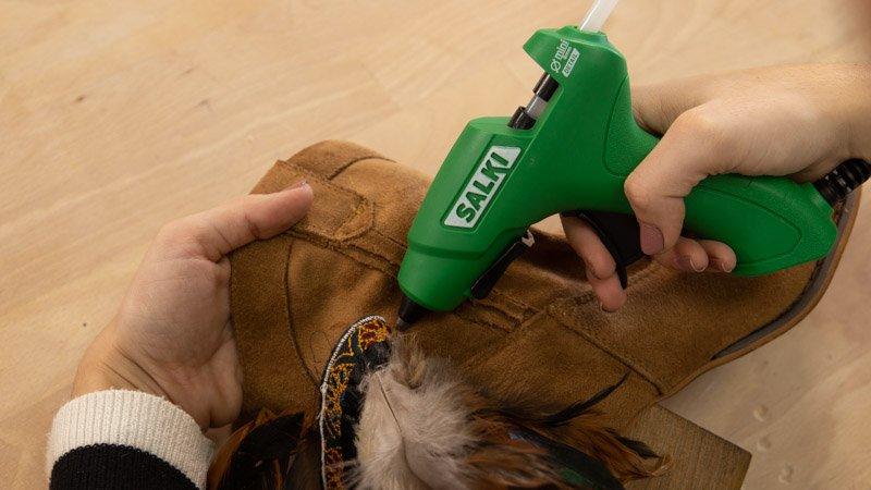 Pegar con la pistola termoencoladora las plumas a las botas.