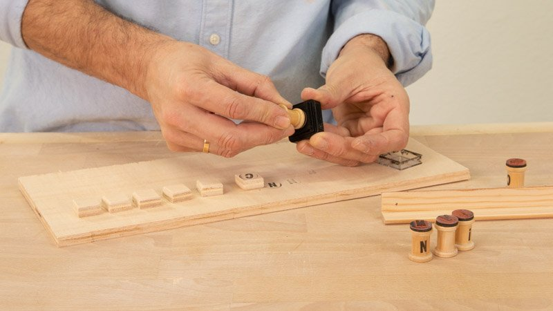 Pintar las letras del cartel de madera con los sellos de letras.
