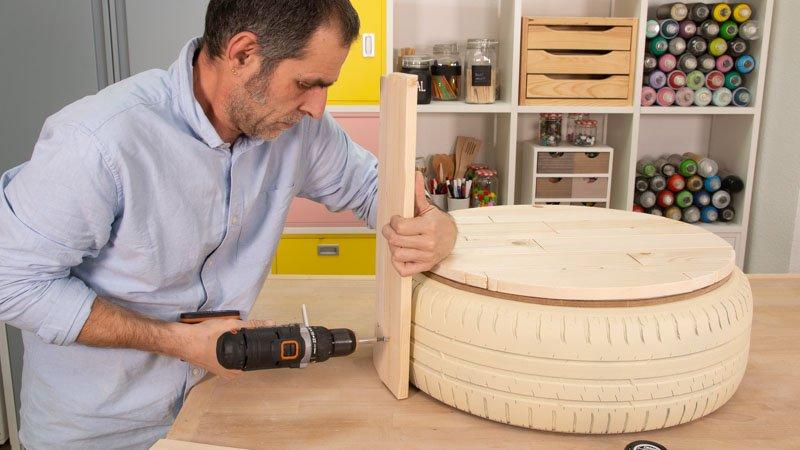 Fijar con el taladro, los tornillos y las tuercas, las tablas que conforman el respaldo del asiento al neumático.