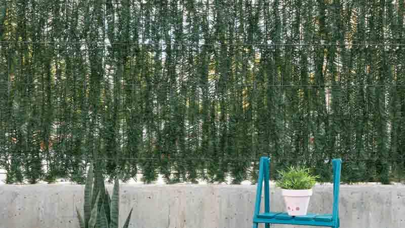 Cómo instalar un seto artificial en ramas en una valla metálica
