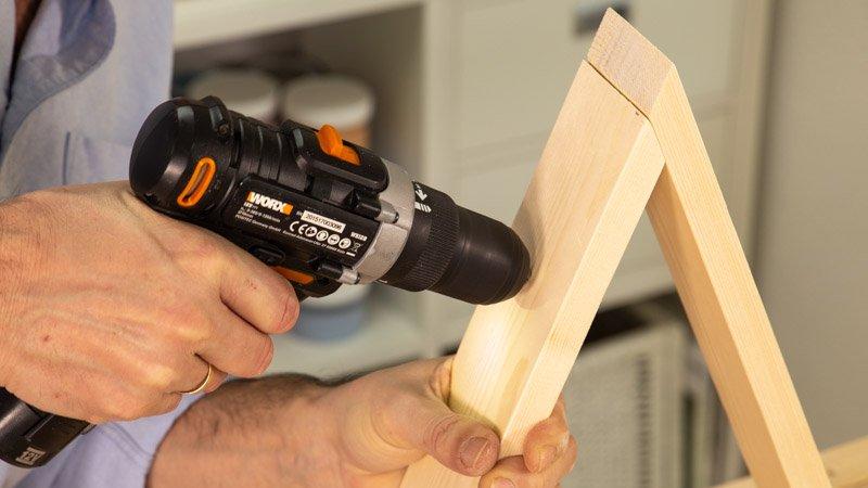 Taladrar la tabla de madera para hacer un agujero.