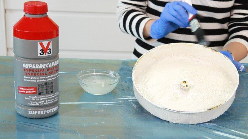 Aplicar decapante a la base del paragüero para quitar la pintura.