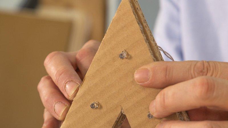 Colocar las luces de Navidad en la estrella de cartón antes de pegarlas.