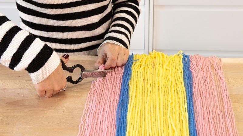 Cortas las tiras de trapillo para darle forma.