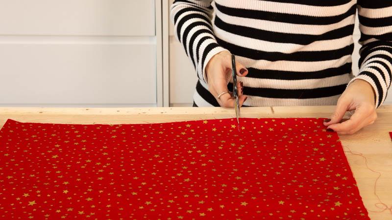 Corta el trozo de tela que va a unir las dos piezas de estrella del cojín.