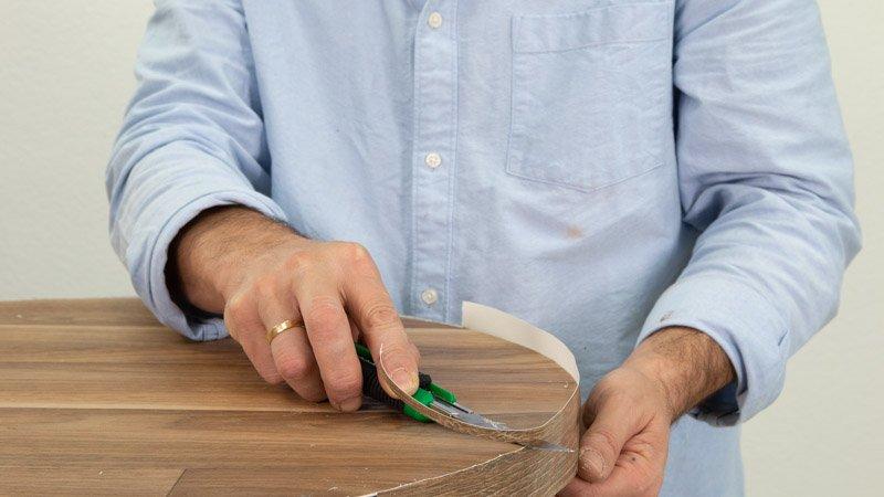 Corta con el cúter el vinilo sobrante del borde del lateral de la mesa alta