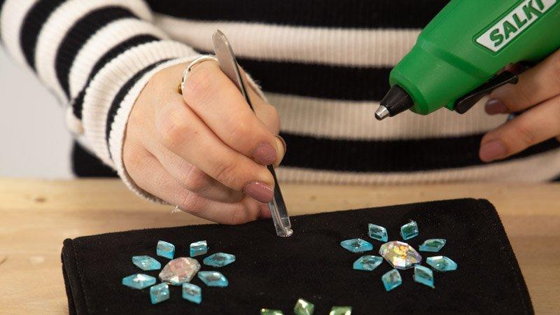 Pega las piedras de colores para customizar tu bolso de fiesta.