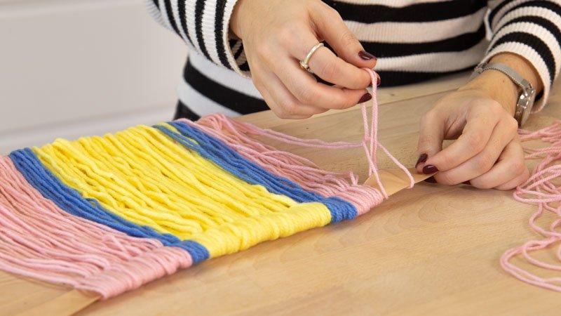 Enrollar las tiras de lana en un lazo para hacer la decoración del espejo