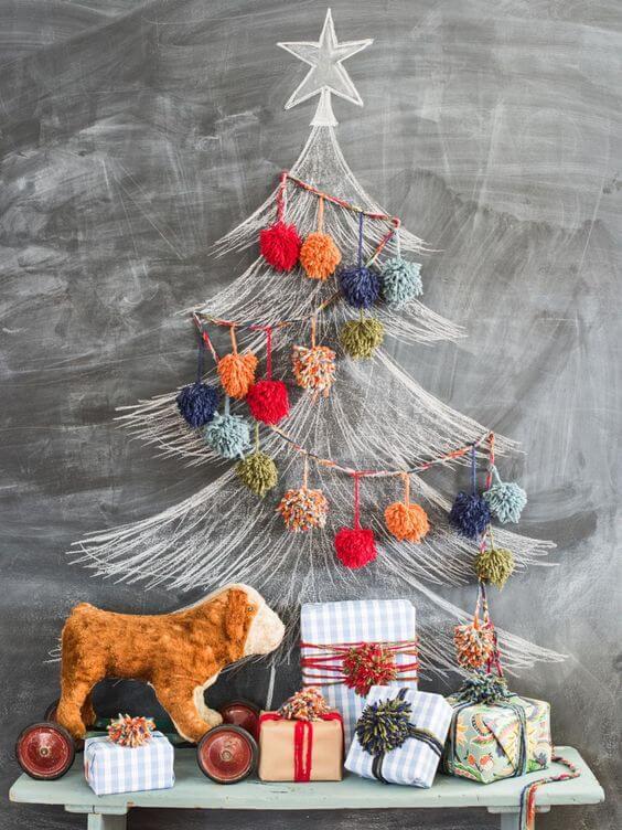 Decoración navideña casera con dibujo de árbol de navidad en una pizarra decorado con guirnalda de pompones