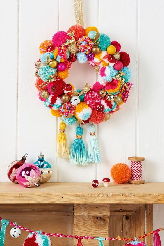 Corona navideña con pompones de lana coloridos