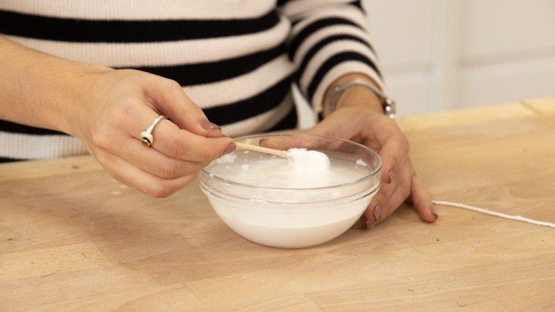 Empapar el hilo de lana en la cola blanca con agua para envolver el globo.