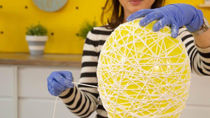 Enrollar el hilo de lana en el globo para hacer la forma de la lámpara.
