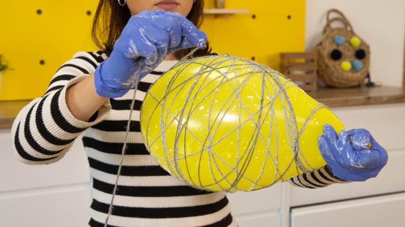 Envolver el hilo de lana en el globo para hacer la forma de la lámpara.