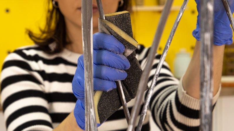 Lijar el paragüero para quitar la pintura restante y el decapante.