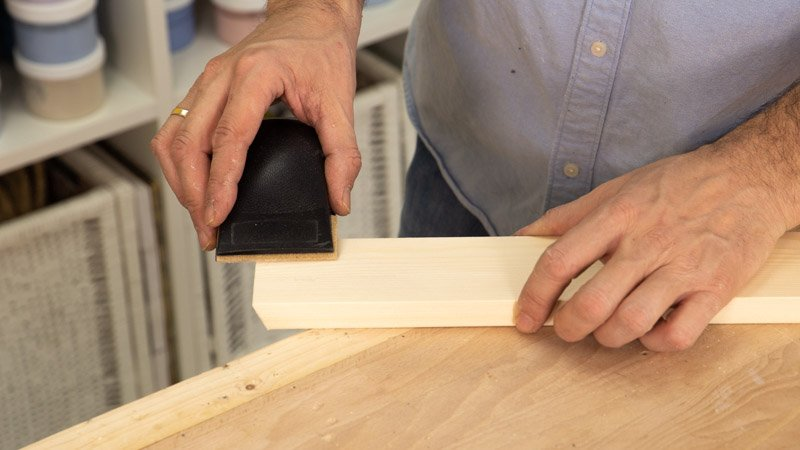Lijar la madera para eliminar las rebabas.