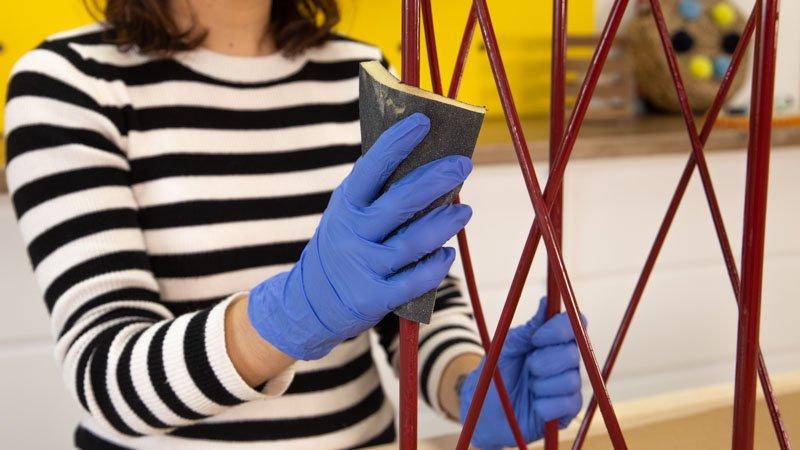 Lijar la primera capa de pintura para aplicar la segunda sobre el paragüero de hierro