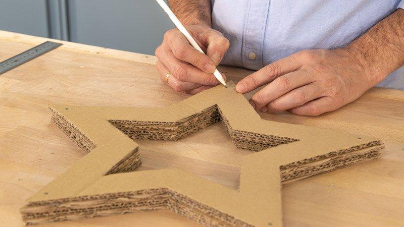 Marcar los agujeros para poner las luces en la estrella de Navidad de cartón
