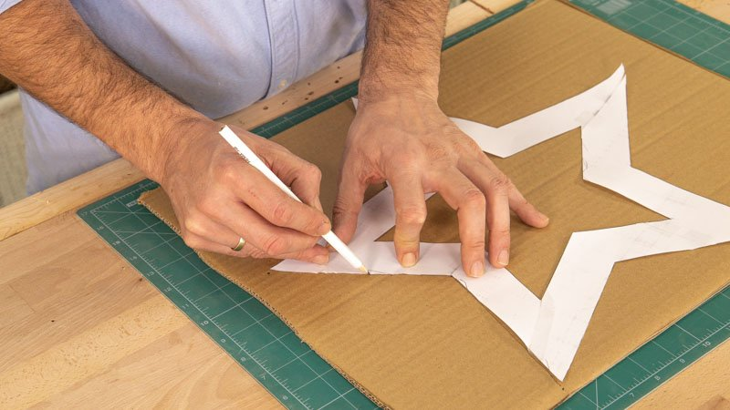 Dibujar la plantilla de estrella en las diferentes piezas de cartón para hacer una estrella de Navidad con luces.