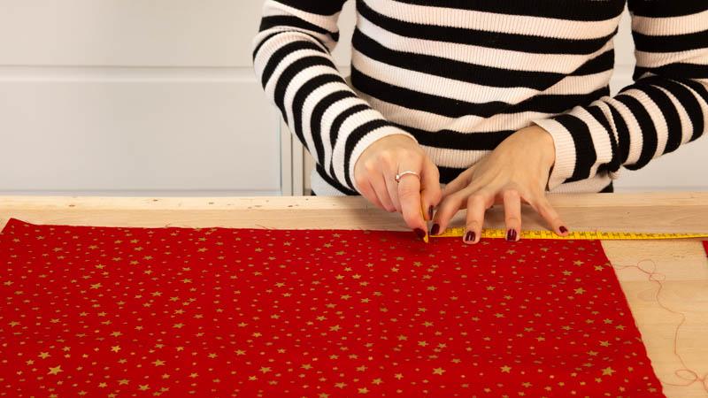 Mide el ancho del trozo de tela que une las piezas de estrella que hacen el cojín.