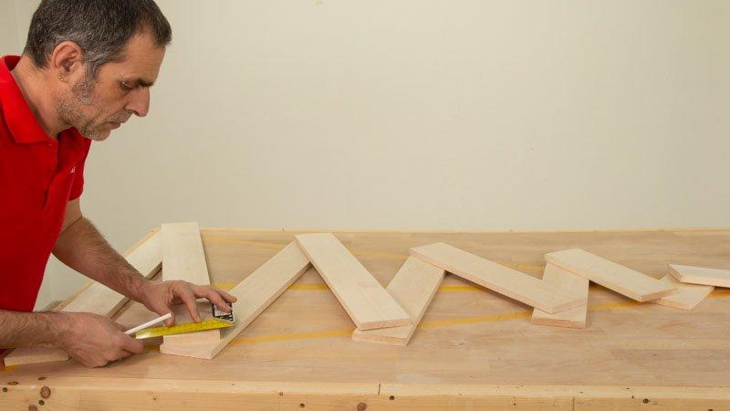 Medir con la regla los cortes de la unión del zigzag de los listones de madera que conforman el árbol de Navidad.