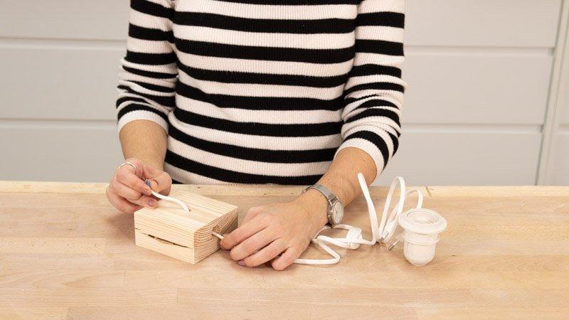 Poner el cable de la lámpara por los agujeros de la madera.