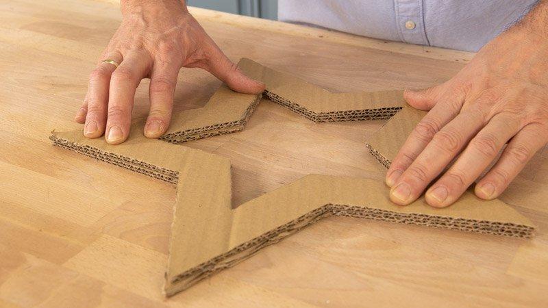 Pegar las distintas piezas de cartón con una pistola termoencoladora y cola caliente para formar la estrella.