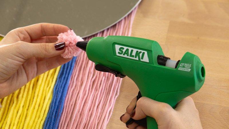 Pegar pompones de lana al trapillo para customizar el espejo