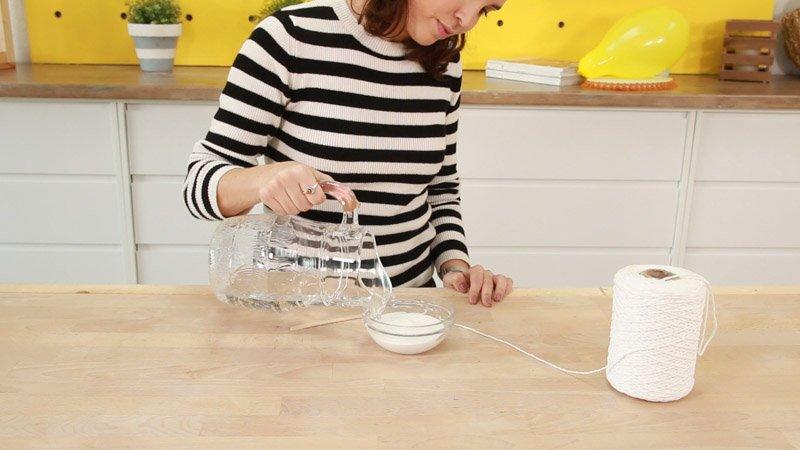 Mezclar agua y cola blanca para mojar el hilo de lana y envolver el globo