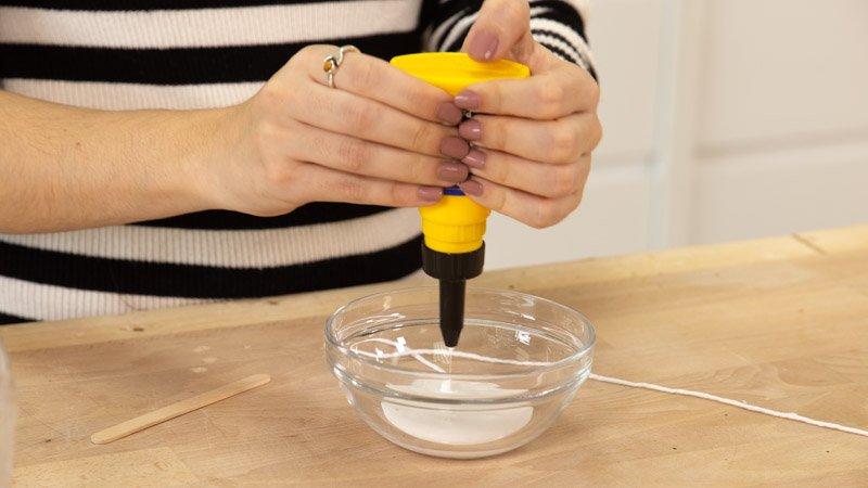 Poner cola en el cuenco de cristal para mezclarla con agua.