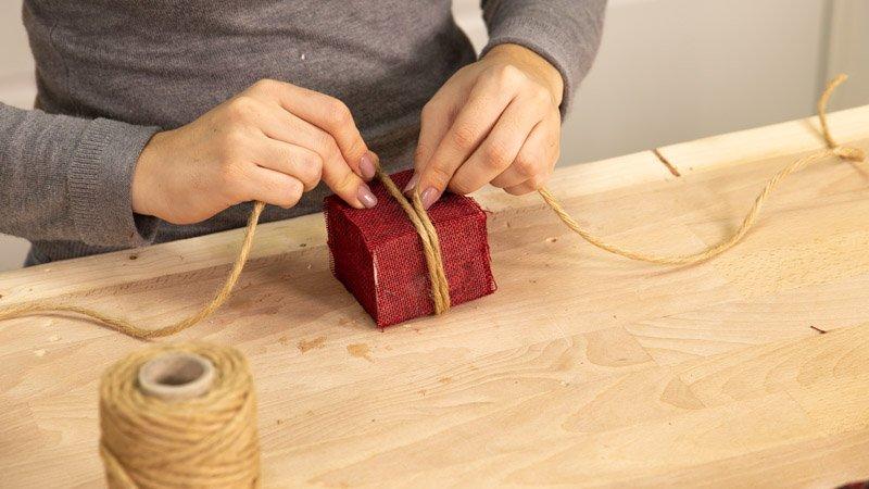 Poner una cuerda a la caja de regalo para cerrarla.