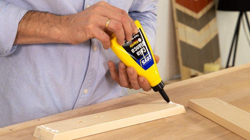 Poner cola para pegar las tablas de madera que forman el árbol.