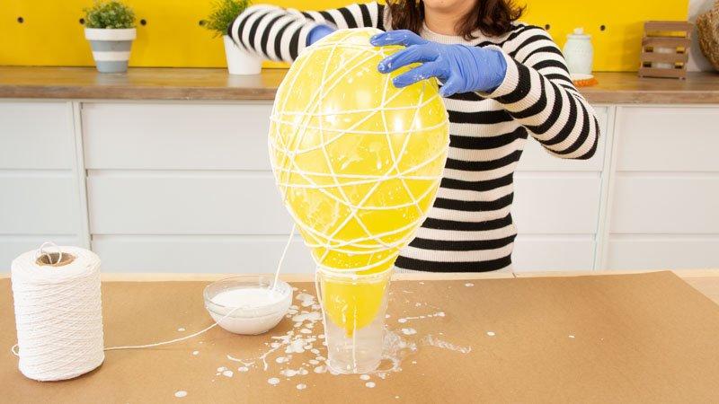 Enrollar todo el hilo empapado en cola blanca y agua alrededor del globo.