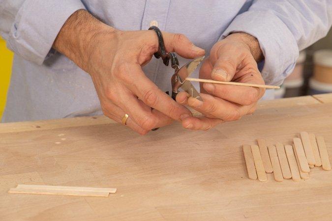 Cortar las piezas para hacer el portavasos de madera con palitos de helado reciclados