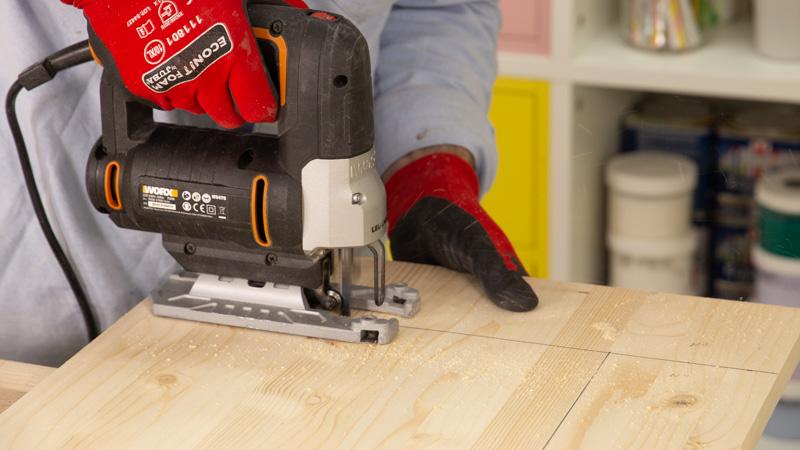 Cortar tablón de madera con una sierra de calar.