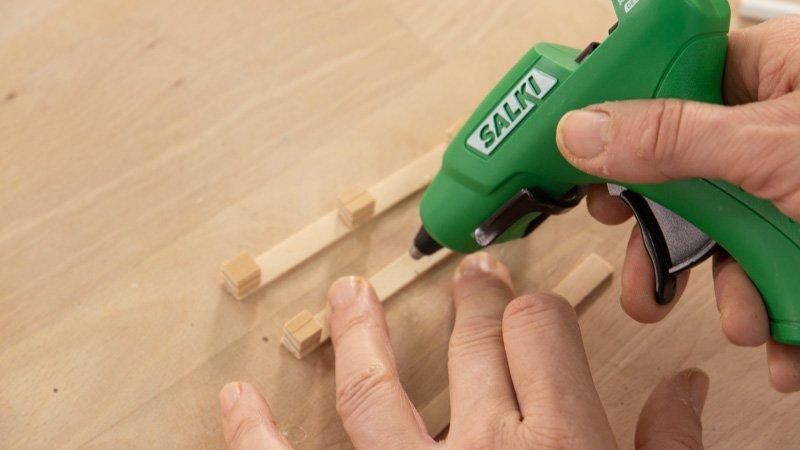 Pegar los taquitos de madera a los palitos para diferenciar los niveles del portavasos.