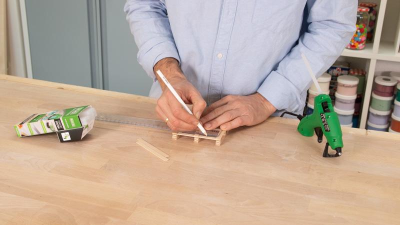 Señalar dónde poner los palos de madera para hacer el soporte del portavasos