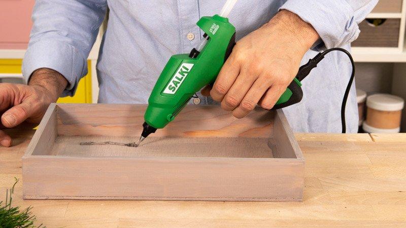 Aplicación de adhesivo termofusible sobre la madera para pegar el césped