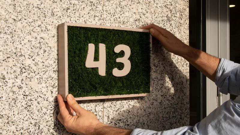 Pegado del número para la puerta en una fachada