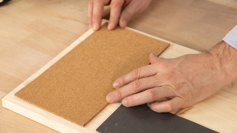 Pegar el corcho en el tablón de madera.