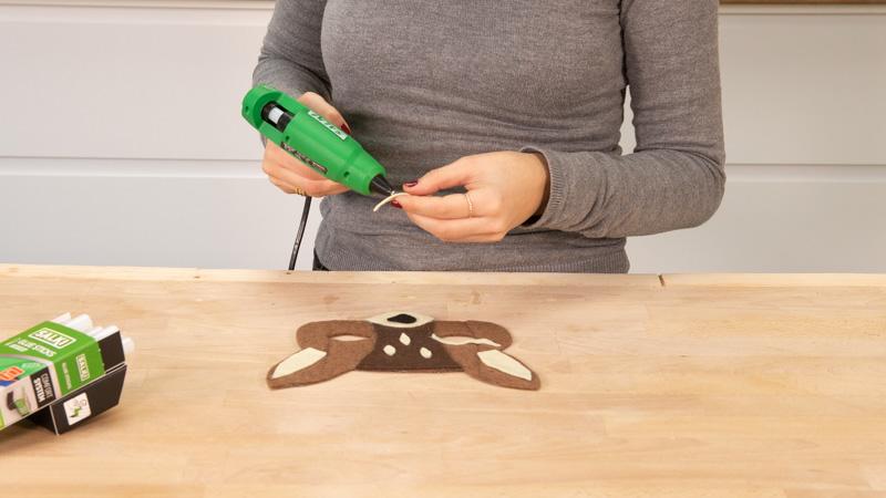 Pegar las piezas de fieltro para decorar la careta.
