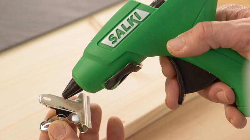 Pegar las pinzas en el tablón de madera con cola caliente.