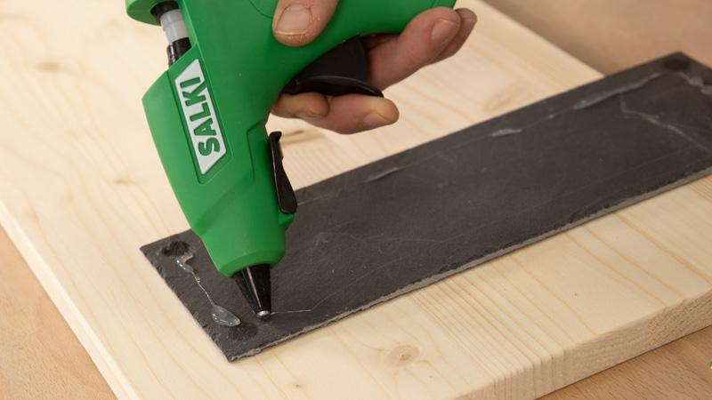 Pegar la pizarra con cola caliente al tablón de madera.