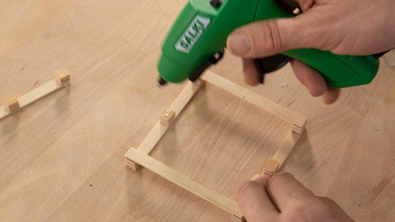 Poner cola caliente para pegar los palitos de madera.